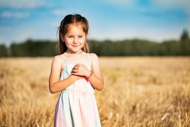Portret uroczej uroczej dziewczynki pozującej w polu podczas żniw w ciepły letni wieczór