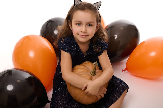 Portret uroczej, uroczej dziewczynki w obręczy z kocimi uszami, ubranej w ciemny kostium karnawałowy wiedźmy, przytula dynię w dłoni, siedzi na białym tle z kolorowymi, czarno-pomarańczowymi kulami powietrznymi