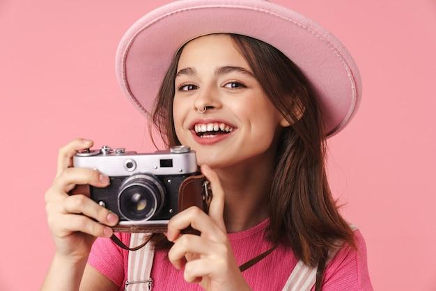 Portret uroczej, uroczej dziewczyny w kapeluszu, uśmiechającej się i używającej kamery retro odizolowanej na różowej ścianie