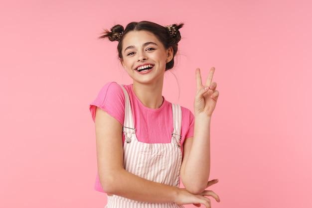 Portret uroczej, uroczej dziewczyny z kolczykiem w nosie pokazującym znak pokoju i uśmiechniętą na białym tle nad różową ścianą