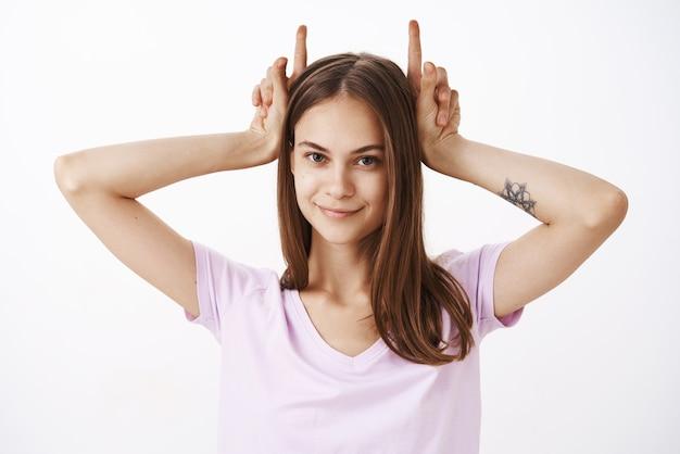 Portret uroczej uroczej i zaufanej europejskiej kobiety z tatuażem na ramieniu, trzymającej palce wskazujące jak rogi demona na głowie i uśmiechającej się z zaintrygowaną, zachwyconą twarzą