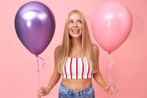 Portret uroczej uroczej studenckiej dziewczyny trzymającej dwa metalowe balony z helem, obchodzi urodziny, zabawę