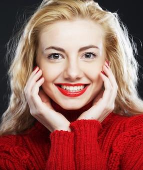 Portret uroczej uśmiechniętej blondynki w czerwonym swetrze