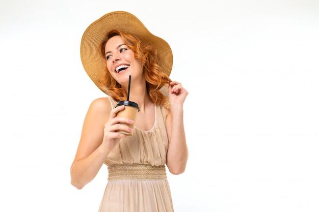 Portret uroczej uśmiechniętej dziewczyny w kapeluszu z papierową filiżanką herbaty na białej ścianie