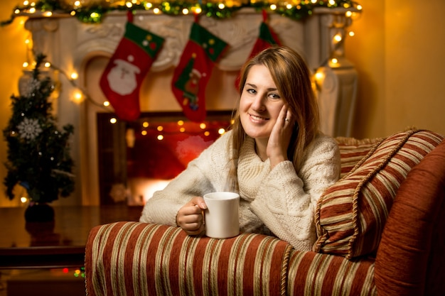 Portret uroczej uśmiechniętej kobiety trzymającej filiżankę herbaty przy kominku
