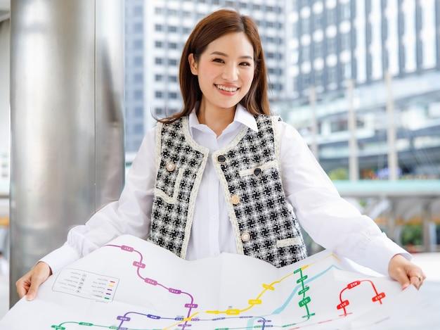 Portret uroczej, uśmiechniętej, młodej, dorosłej azjatyckiej kobiety w eleganckich, casualowych, czarno-białych ubraniach, opierając się o słup, trzymając papierową mapę metra i patrząc na kamerę z rozmytym tłem