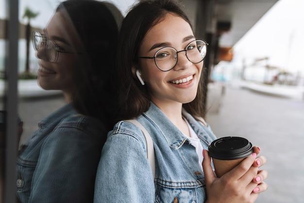 Portret uroczej uśmiechniętej nastolatki w okularach i słuchawkach trzymających papierowy kubek kawy na wynos podczas spaceru na świeżym powietrzu