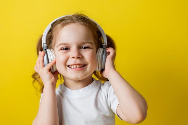 Portret uroczej, wesołej dziewczynki słuchającej muzyki z lekcjami audio w białych słuchawkach