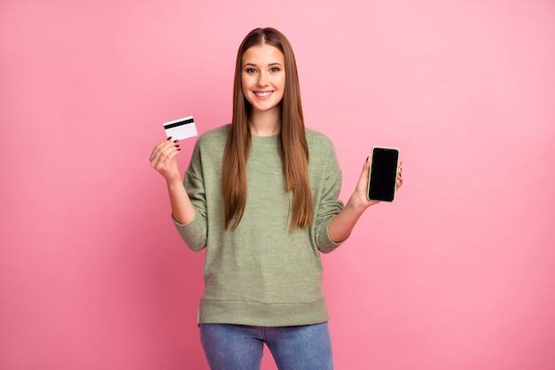 Portret uroczej wesołej ładnej dziewczyny trzymać kartę kredytową smartfona