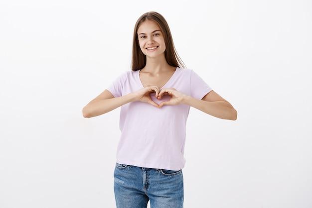 Portret uroczej, wesołej młodej dziewczyny rasy kaukaskiej w swobodnej koszulce, uśmiechającej się radośnie, wyrażającej miłość, pokazującej gest serca na klatce piersiowej, wyznającej ciepłe uczucia rodzinie