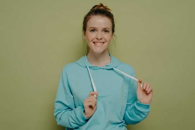 Portret uroczej zalotnej nastoletniej dziewczyny, która gryzie dolną wargę bawiąc się sznurkami z kapturem, stojąc przed kamerą na kolorowym tle w studio, kobieta czuje się zabawna i beztroska