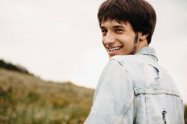 Portret uroczy mężczyzna ubrany w dżinsową kurtkę, patrząc przez ramię, śmiejąc się z aparatu na zewnątrz.