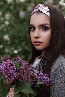 Portret uroczy przetargu młoda kobieta w efektownej chustce w modny płaszcz z luksusowym bukietem bzu na tle zielonych liści w parku. urocza dziewczyna z fioletowymi kwiatami pozuje na zewnątrz na wiosnę