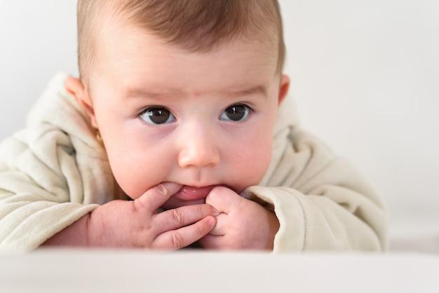 Portret uroczy uśmiechnięty dziecko gryźć jej własnych palce stawia jej pięść w jej usta.