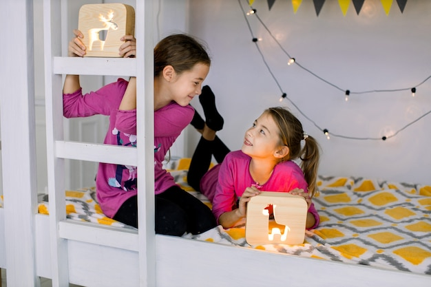Portret uroczych dzieci, dwóch małych ślicznych dziewczynek, bawiących się drewnianymi lampkami nocnymi w stylowo urządzonym łóżku piętrowym. dzieci, zabawki, lampki nocne, koncepcja czasu wieczornego.