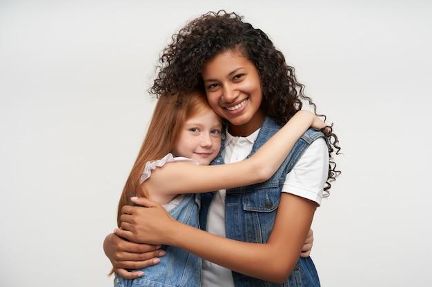 Portret uroczych młodych kobiet w codziennych ubraniach, obejmujących się delikatnie i pozytywnie wyglądających z delikatnym uśmiechem, stojących na białym tle