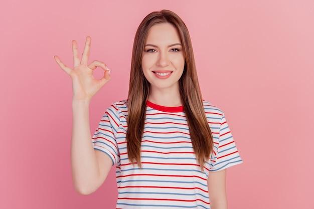 Portret uroczych, uroczych palców promotorki pokazuje okey gest na różowym tle