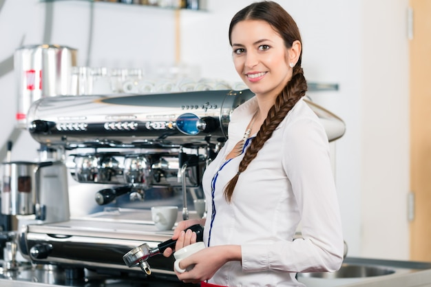 Portret uśmiecha się blisko kawowej maszyny młoda kelnerka