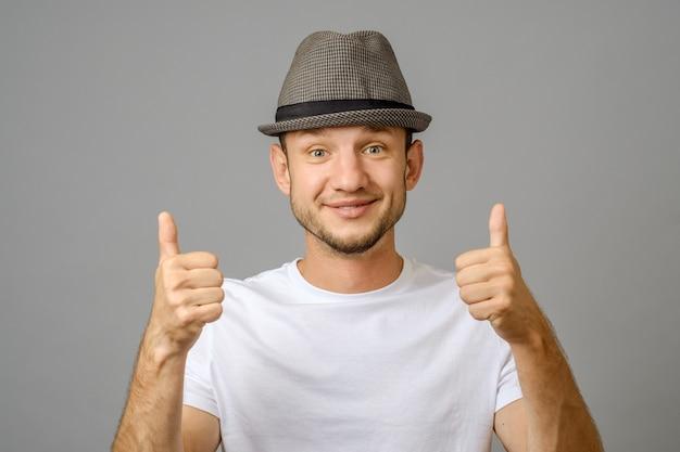 Portret uśmiecha się dwa aprobaty i pokazuje mężczyzna