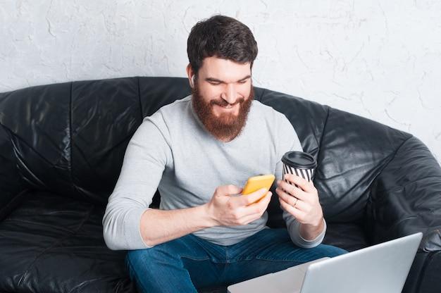 Portret uśmiecha się jego smartphone i używa młody człowiek podczas gdy siedzący na kanapie w biurze