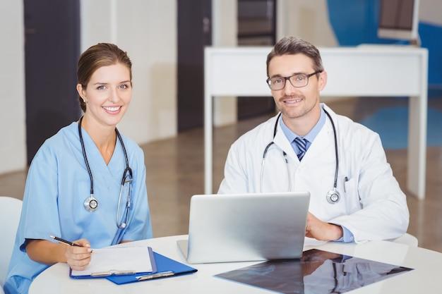 Portret uśmiechać się lekarki siedzi przy biurkiem