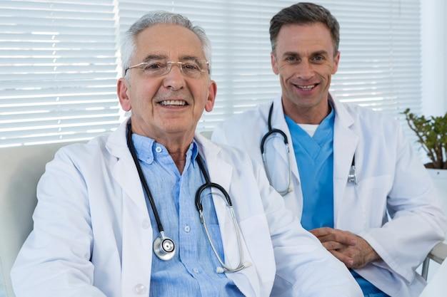 Portret uśmiechać się lekarki siedzi przy stołem
