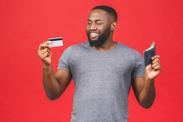 Portret uśmiechający się afroamerykanin czarny brodaty mężczyzna pokazuje kartę kredytową i portfel z pieniędzmi