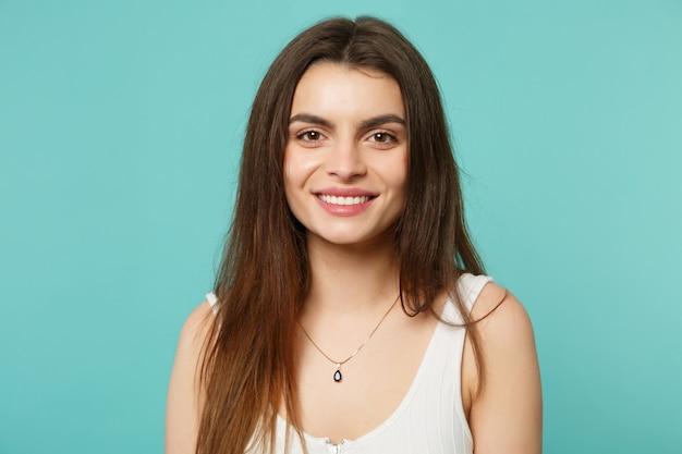 Portret uśmiechający się atrakcyjna młoda kobieta w lekkie ubrania dorywczo patrząc aparat na białym tle na tle niebieskiej ściany turkus w studio. ludzie szczere emocje, koncepcja stylu życia. makieta miejsca na kopię.
