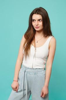 Portret uśmiechający się atrakcyjna młoda kobieta w lekkie ubrania dorywczo patrząc na bok na białym tle na tle niebieskiej ściany turkus w studio. ludzie szczere emocje, koncepcja stylu życia. makieta miejsca na kopię.
