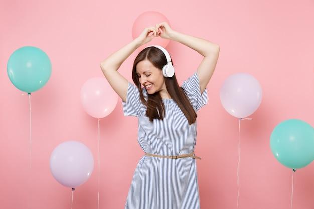 Portret uśmiechający się atrakcyjna młoda kobieta ze słuchawkami w niebieskiej sukience słuchania muzyki tańczy na pastelowym różowym tle z kolorowych balonów. urodziny wakacje, ludzie szczere emocje.
