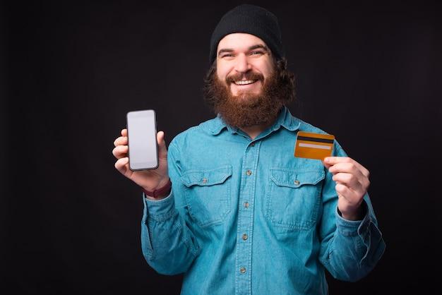 Portret uśmiechający się brodaty mężczyzna pokazuje kartę kredytową i smartfona