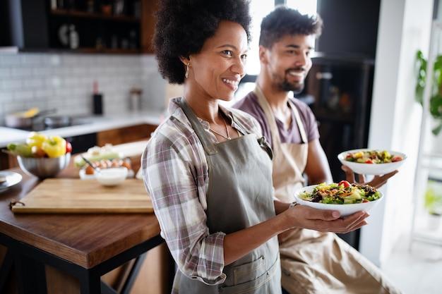 Portret uśmiechający się kucharzy w kuchni. zdrowa żywność, gotowanie, ludzie, koncepcja kuchni