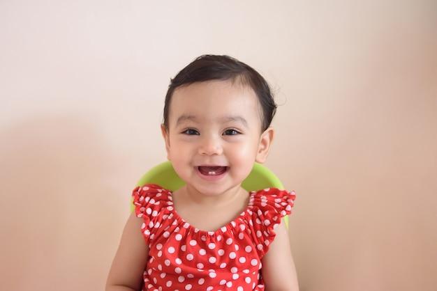 Portret uśmiechający się ładny mały azjatycki dziewczynka nosić czerwoną sukienkę, usytuowanie na łóżku i patrząc na kamerę, na białym tle na tle, koncepcja wyrażenia dziecka