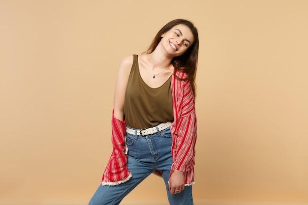 Portret uśmiechający się ładny młoda kobieta w ubraniach casual, stojąc i patrząc na bok na białym tle na tle pastelowej beżowej ściany w studio. ludzie szczere emocje, koncepcja stylu życia. makieta miejsca na kopię.