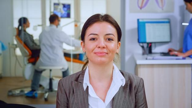 Portret uśmiechający się młody pacjent patrząc na kamerę internetową siedzącą na krześle w poczekalni kliniki stomatologicznej, podczas gdy lekarz pracuje w tle. asystent stomatologa piszący na komputerze w gabinecie stomatologicznym