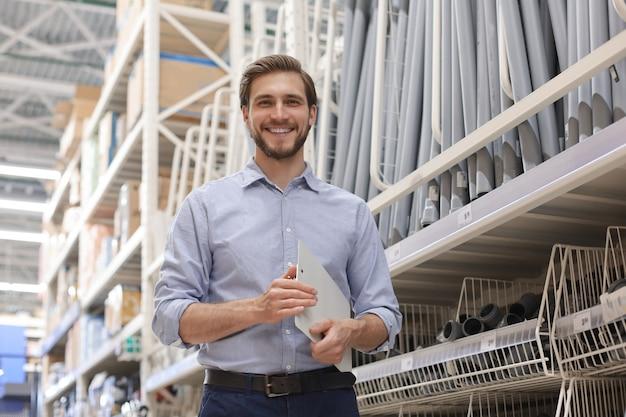 Portret uśmiechający się młody pracownik magazynu, pracujący w hurtowni gotówki i przenoszenia.
