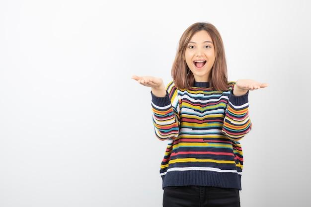 Portret uśmiechający się model młodej kobiety pokazujący otwarte dłonie.
