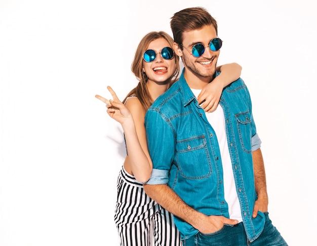 Portret uśmiechający się piękna dziewczyna i jej przystojny chłopak śmiejąc się. szczęśliwy wesoły para w okulary przeciwsłoneczne. i pokazując znak pokoju