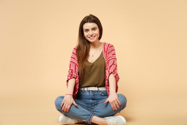 Portret uśmiechający się piękna młoda kobieta w ubranie siedzące, patrząc na kamerę na tle pastelowej beżowej ściany w studio. ludzie szczere emocje, koncepcja stylu życia. makieta miejsca na kopię.