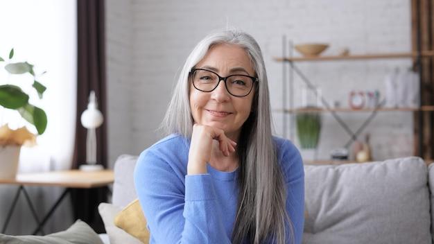 Portret uśmiechający się piękna starsza siwowłosa kobieta patrząc na kamery.