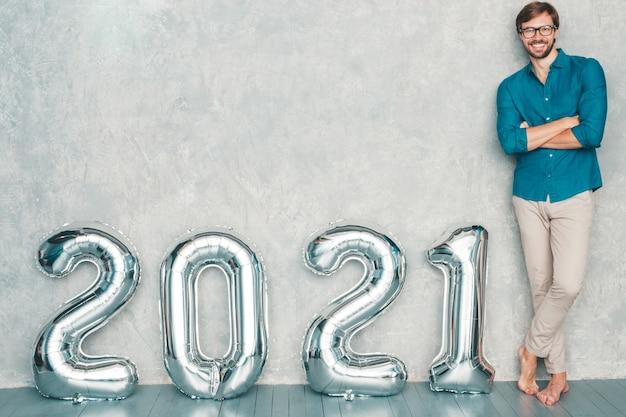 Portret uśmiechający się przystojny mężczyzna pozowanie w pobliżu ściany. seksowny brodaty mężczyzna stojący w pobliżu srebrnych balonów 2021. szczęśliwego nowego 2021 roku. cyfry metaliczne 2021