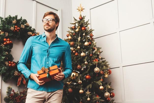 Portret uśmiechający się przystojny mężczyzna trzyma prezent. seksowny brodaty mężczyzna pozowanie w pobliżu choinki z teraźniejszością.