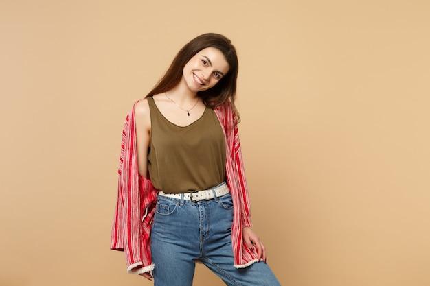 Portret uśmiechający się radosny młoda kobieta w ubranie stojące i patrząc na kamerę na białym tle na tle pastelowej beżowej ściany w studio. ludzie szczere emocje, koncepcja stylu życia. makieta miejsca na kopię.