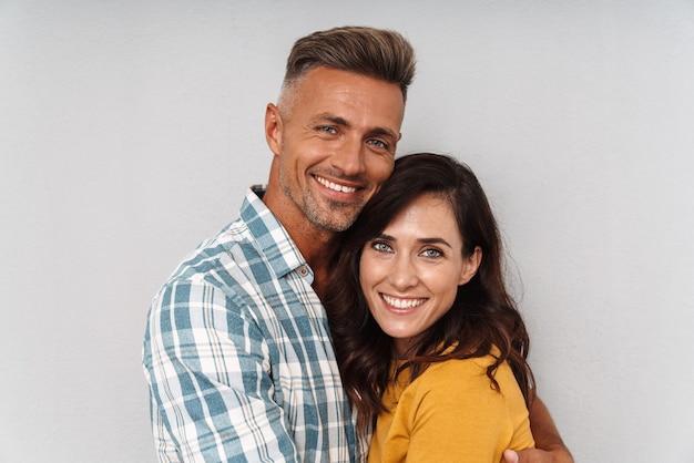Portret uśmiechający się szczęśliwy dorosłych miłości para na białym tle nad szarą ścianą przytulanie.