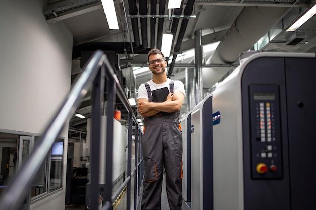 Portret uśmiechający się typograf stojący przy maszynie drukarskiej w drukarni.