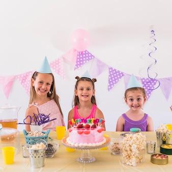 Portret uśmiechnięci dzieciaki jest ubranym partyjnego kapeluszowego świętuje przyjęcia urodzinowego