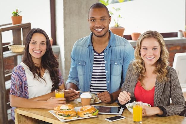 Portret uśmiechnięci koledzy ma śniadanie w biurze