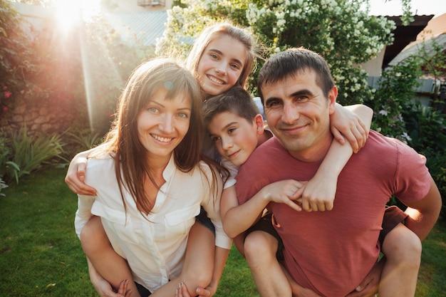 Portret uśmiechnięci rodzice z ich dziećmi przy parkiem