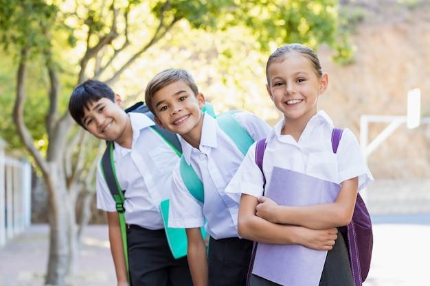 Portret uśmiechnięci szkolni dzieciaki stoi w kampusie