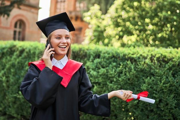 Portret uśmiechnięta absolwentka dzwoniąca przez telefon komórkowy w szacie ukończenia szkoły z dyplomem.
